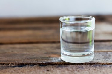 Close-Up Of Water In Drinking Glass On Wooden Table