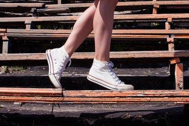Woman model feet wearing sneakers walking down the bench