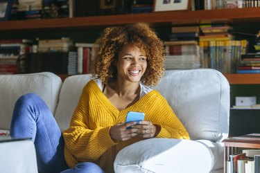 Happy young woman with cell phone sitting on sofa at home