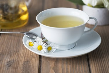 Herbal tea in a white cup with a saucer.