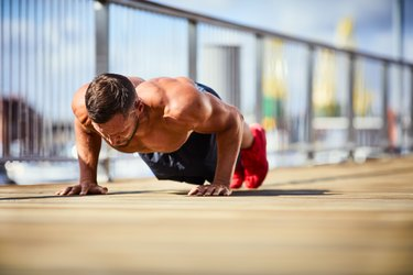 Portrait of a athletic man doing push-ups outside