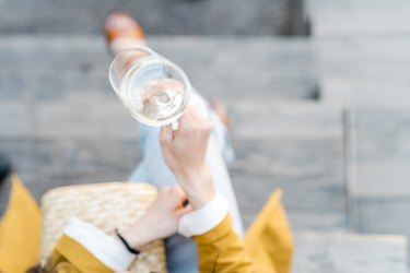 Overhead view of a woman with a glass of white wine