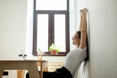 Attractive young businesswoman relaxing, stretching at desk in home office