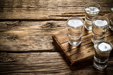 four shot glasses with vodka on a wooden board
