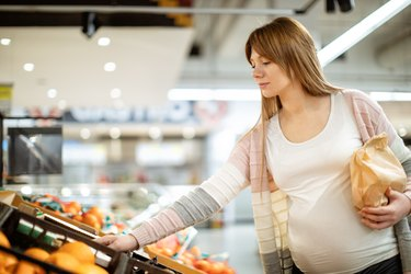 Beautiful pregnant woman shopping in supermarket