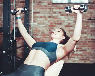 Young sports woman doing exercises with dumbbells in gym. Toned photo