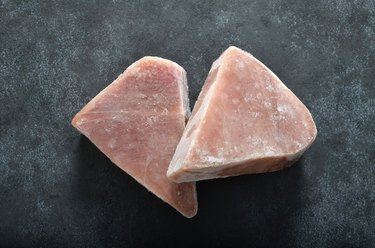 Two frozen tuna fish steaks on dark backgound shot from above