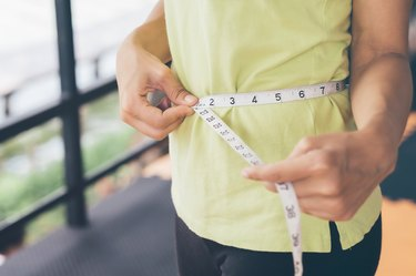 A woman measuring her waist size with a tape measure