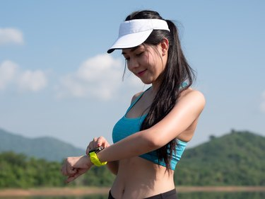 Young Asian woman body slim fit fitness sexy in sportwear setting up the fitness smart watch for running on road. Sportswoman, Health lifestyle Concept.
