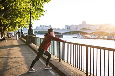 Young sporty man with earphones stretching on a railing outside in a London city.