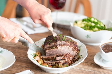 Woman cutting tender roast beef recipe