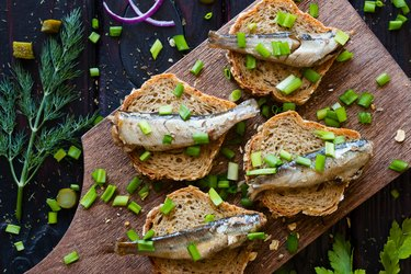 sandwich with sardines for bone health sprinkle with onions on a cutting board