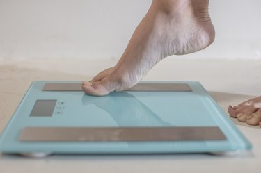 Young woman stepping onto weighing scales, close up of foot
