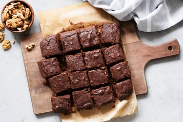 Chocolate brownie squares on cutting board, top view