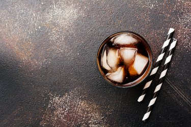 Cold Cola in glass with ice cubes on dark old concrete background. Top view.