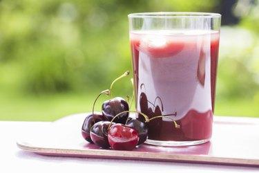 Glass of tart cherry juice in garden
