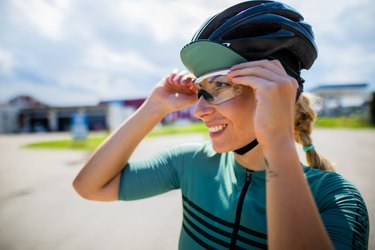 woman cyclist adjusting her bike helmet and goggles outside