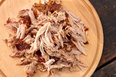 Pulled pork on round wooden board