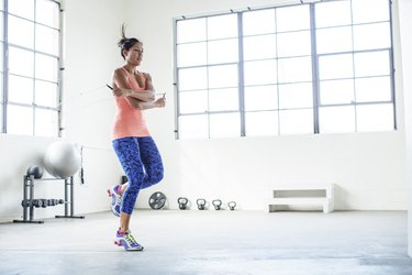 Female athlete exercising with jumping rope in gym