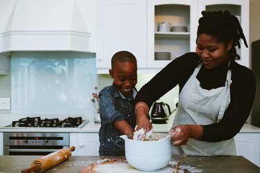 Mother and son in kitchen mixing bread dough