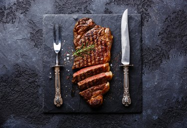 Sliced meat steak Striploin with knife and fork carving set