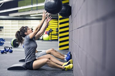 Doing a medicine ball wall ball with crunch during CrossFit AMRAP workout