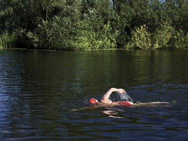 Woman swimming freestyle swimming stroke in a river surrounded by trees
