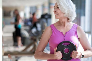 Delighted smiling woman exercising with sport equipment.