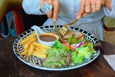 High Angle View Of Woman Eating Food On Table