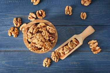 Bowl and scoop with tasty walnuts on color wooden table