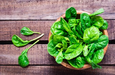 Fresh baby spinach leaves in a bowl on a wooden table.