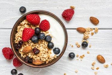 bowl of oat granola with yogurt, fresh raspberries, blueberries and nuts