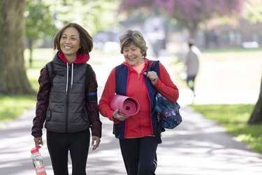 Active senior women friends with yoga mat walking in park