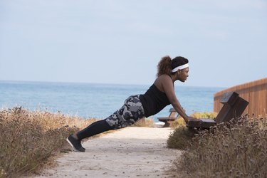 A woman on morning workout outdoors. Incline press-up.