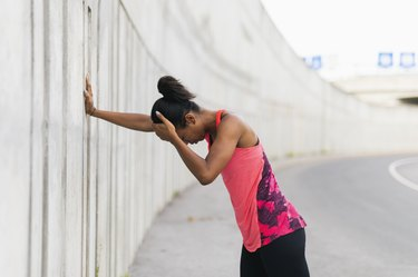 Female runner leaning against a wall after getting a headache