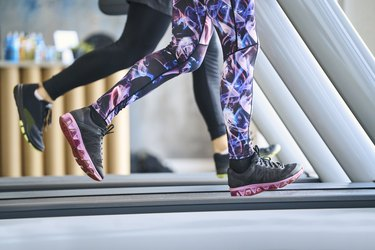 Close-up of people running on treadmill at gym