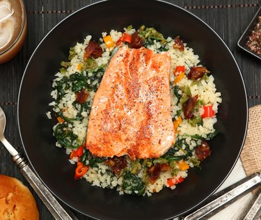 Top view of a bowl of salmon over riced cauliflower
