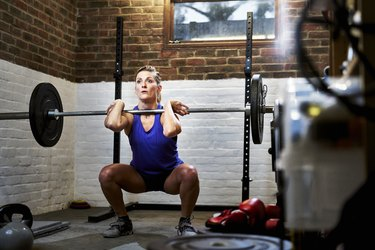 Woman exercising in home gym in converted garage performing a squat or clean