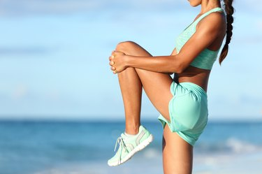 Runner stretching leg during outdoor warm-up on beach before run