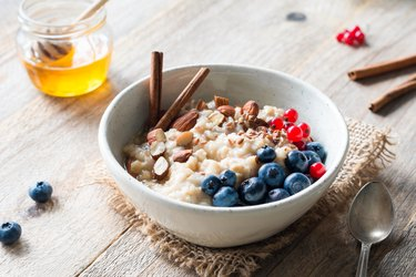 Oatmeal porridge bowl with fruits, nuts and cinnamon in bowl