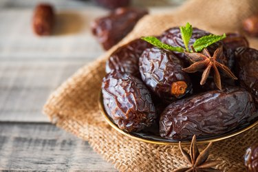 Ramadan food and drinks concept. Dates fruit and green Mint leaves in a bowl on wooden table background.