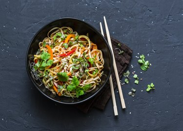 Pad Thai vegetarian vegetables udon noodles in a dark background, top view. Vegetarian food in asian style. Copy space