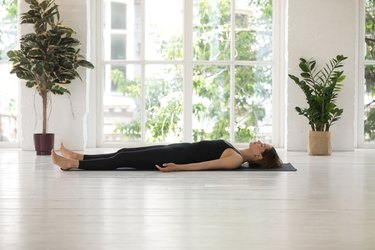 Woman demonstrating how to do the yoga pose Corpse Pose (Savasana)