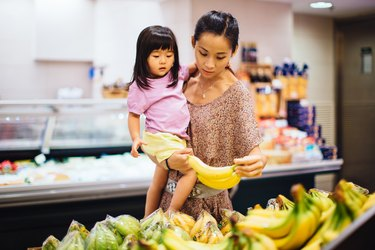 Mom and toddler girl choosing bananas in supermarket to help potassium deficiency