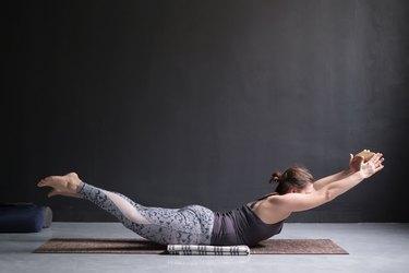 Woman practicing yoga, stretching in Salabhasana exercise, Double Leg Kicks pose