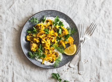 Roasted turmeric cauliflower with greek yogurt dressing. Delicious healthy food on a grey background, top view