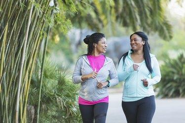 two black women in a park walking to lose belly fat
