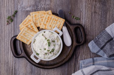 Traditional soft cheese with thyme and crackers on plate