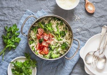 One pot orzo primavera. Orzo pasta with asparagus, broccoli, green peas and cream in a saucepan.