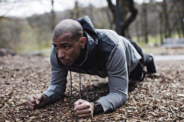 Determined male athlete performing plank position in forest